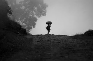 Black and White photo of child carrying load